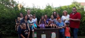 Auf dem Foto einige Kinder und Eltern am neuen Hochbeet. Herr Stiede, Elternbeirat, übergibt einen Umschlag mit Geld an Frau Ott.